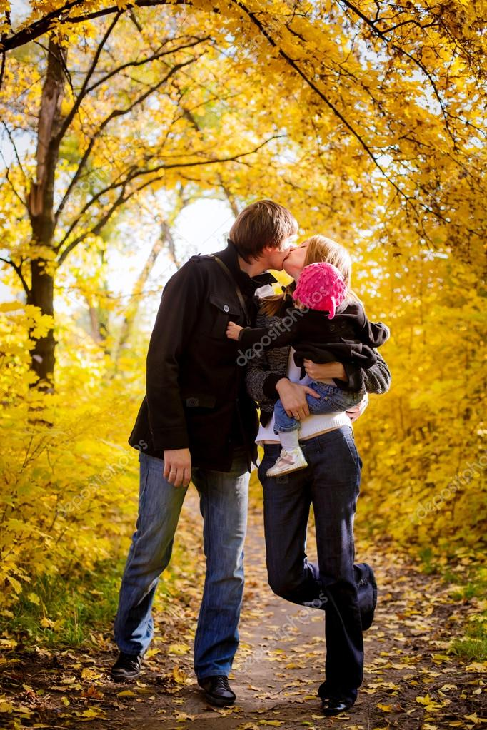 Family with child kissing in the autumn park