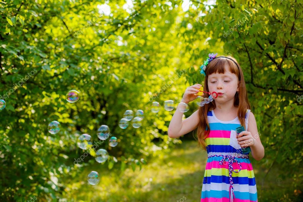 Girl blowing soap bubbles.