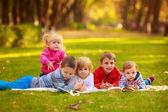 Fotografie děti čtení knihy venku