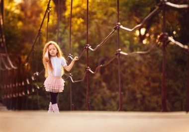 Little  girl walking on a bridge