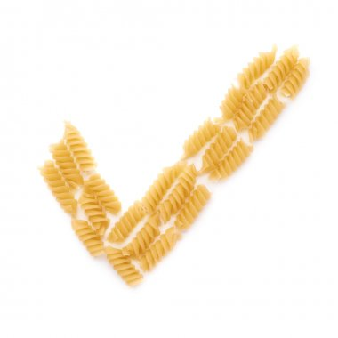 Yes tick sign symbol mark made of dry rotini pasta over isolated white background