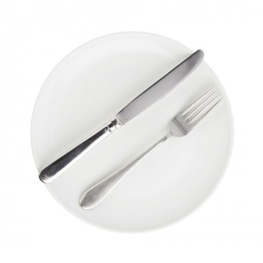 Knife and fork over the plate isolated