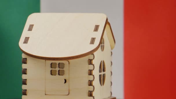 Small wooden house, Italy flag on background. Real estate concept, soft focus