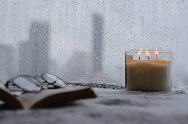 Yanan aroma mumu pencere kenarına konur. Muson mevsiminde yağmur damlası olur ve şehir arka planında bulanıklık olur. Zen ve rahatlama konsepti.