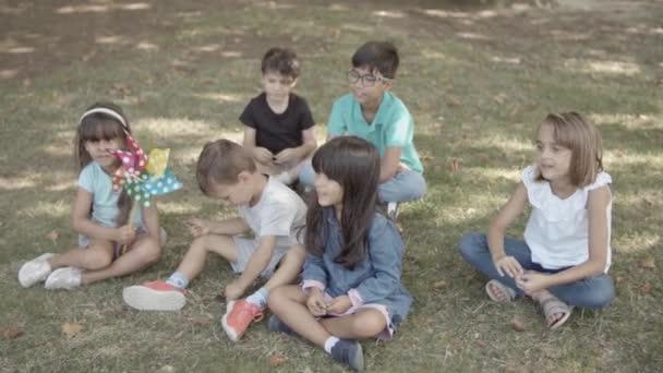 Multietnické děti sedící spolu na trávě v parku