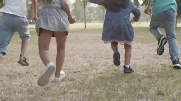 Pohled zpět na šťastné děti soutěžící v rychlosti v parku