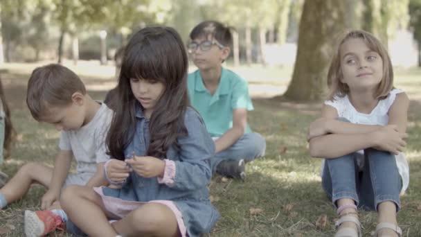 Multiethnische Mädchen und Jungen sitzen gemeinsam auf Gras im Park