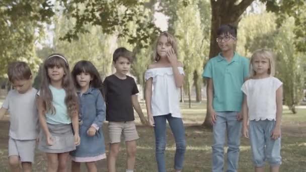 Boldog többnemzetiségű gyerekek állnak együtt nyersen és ugrálva
