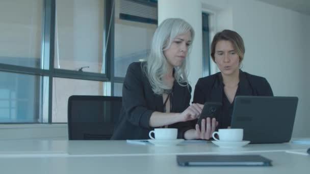 Vážní kolegové z kanceláře, kteří spolu sedí u notebooku