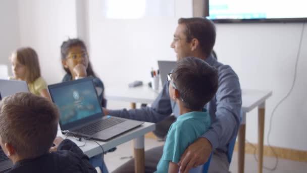 Iskolai tanár ül íróasztal mellett gyermekek
