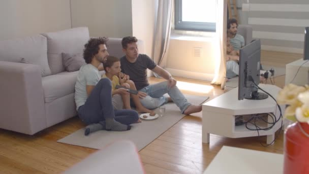 Gay parents and child eating cookies and watching movie