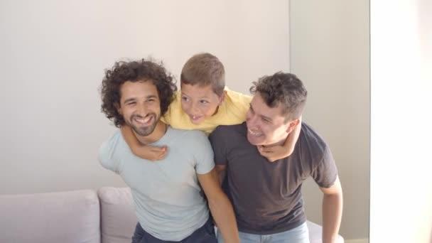 Vidám fiú és két apja élvezik az otthoni tevékenységet