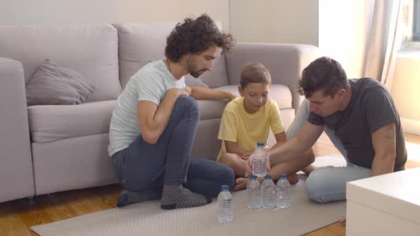 Zwei fröhliche Väter und ein Junge sitzen zu Hause auf dem Boden