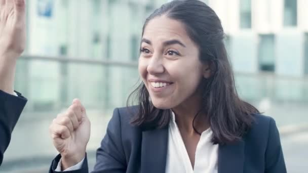 Happy female employee discussing job success with colleague