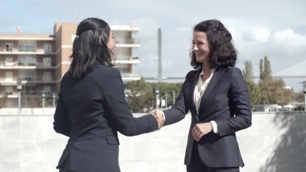 Content beautiful businesswomen handshaking