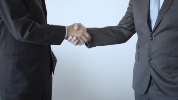Mužští obchodní partneři stojící u bílé zdi