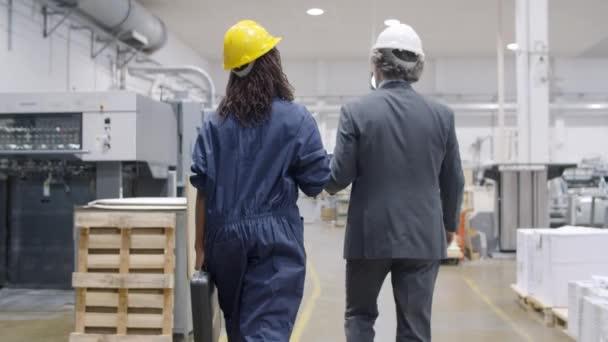 Alter Inspektor und schwarze Fabrikangestellte