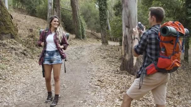 Férfi túrázó kamerával képeket készít a boldog barátnőjéről.