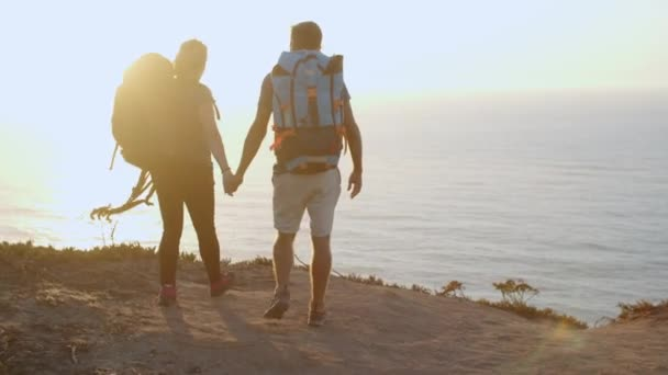 Happy couple with camping backpacks walking on mountain path