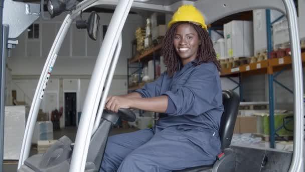 Medium shot of woman in helmet sitting in forklift