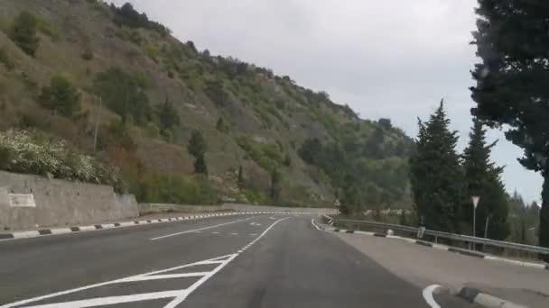 Jízda na Krymu 3. května2020. Malebná krajina na jižním pobřeží. Šedý, zatažený den. Jede po jižní pobřežní dálnici ze Sevastopolu do Jalty. Koncept cestování autem.