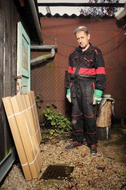 Yazlık evin arka bahçesinde raflı kutuları açan adam.