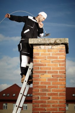Chimney sweep man in work uniform cleaning brick style chimney on building roof stock vector
