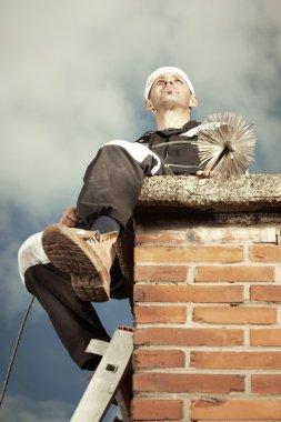 Chimney sweep man on brick chimney