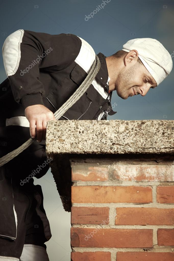 Chimney sweep man at work outdoor