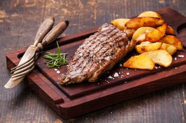 Well done grilled New York steak with roasted potato
