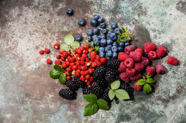Assorted fresh berries with leaves