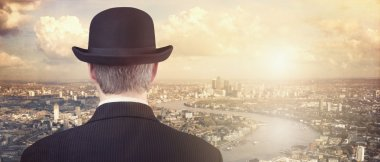 Businessman looking at sunset and city skyline