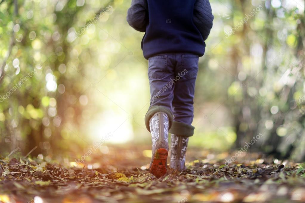 Boy walking on country footpath