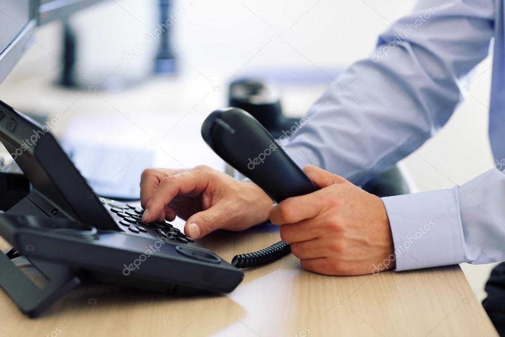 Man dialing telephone keypad