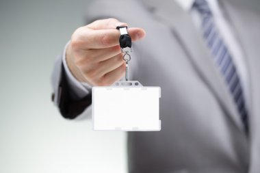 Businessman holding blank ID badge