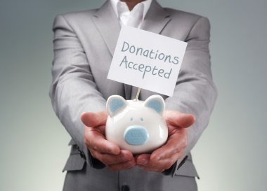Businessman holding piggy bank for charity