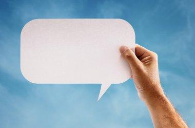 Hand holding a blank speech bubble sign