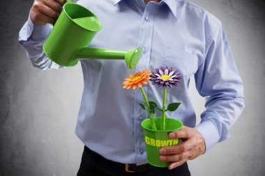 businessman with watering can investing in business