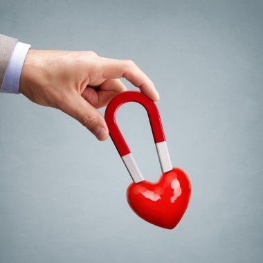male hand holding magnet with heart