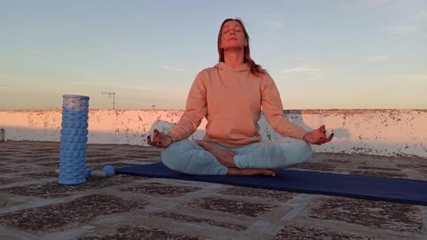 Erwachsene sportliche Frau meditiert auf dem Dach ihres Hauses, Zen-Yoga-Meditationspraxis in Outdoos