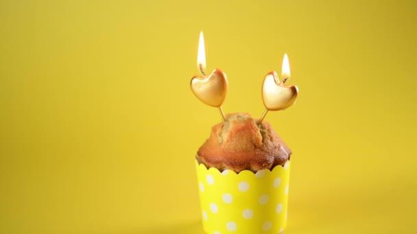 4k Valentin napi cupcake vagy muffin két arany szív alakú gyertyák sárga díszítés formájában sárga alapon, Ünneplés Valentin-nap. Nyaralás, házaspár évfordulója, születésnap, monokróm