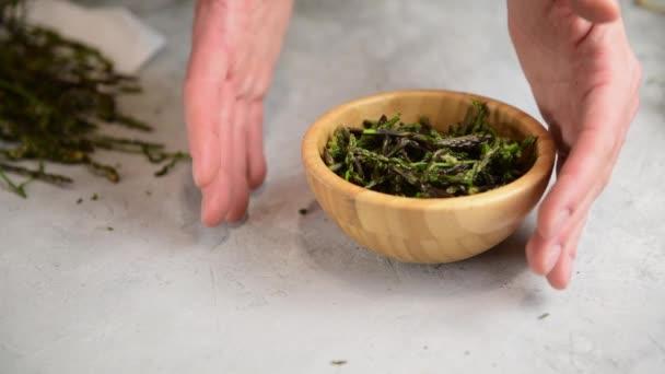 autentické ženské ruce ukazující divoký chřest připravený vařit na šedém stole. Přirozená středomořská divoká bylina k jídlu