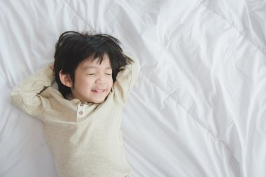 asian child lying on white bed