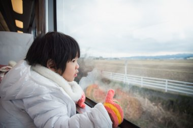 Happy asian child looking out train window outside