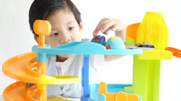 Roztomilé Asijské dítě hraje autíčka na bílém pozadí