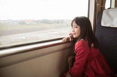 Little asian girl looking through window.