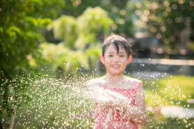 Blur of Asian child playing with water hose