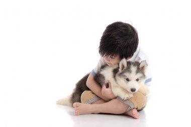 Cute asian boy sitting with siberian husky puppy