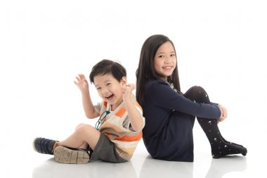 Two  happy asian children sitting and leaning on each othe