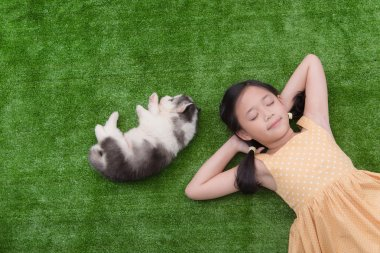 Cute asian girl lying with puppy